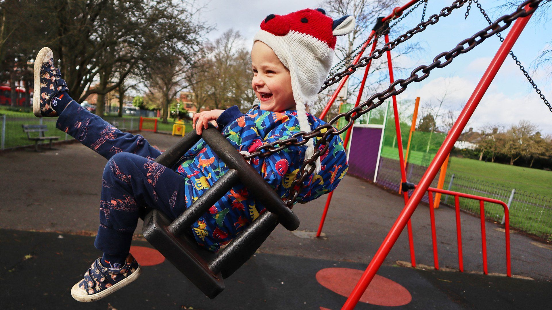 A young boy swings on a swing, laughing. Taken on a Canon EOS M50 by Katja Gaskell.